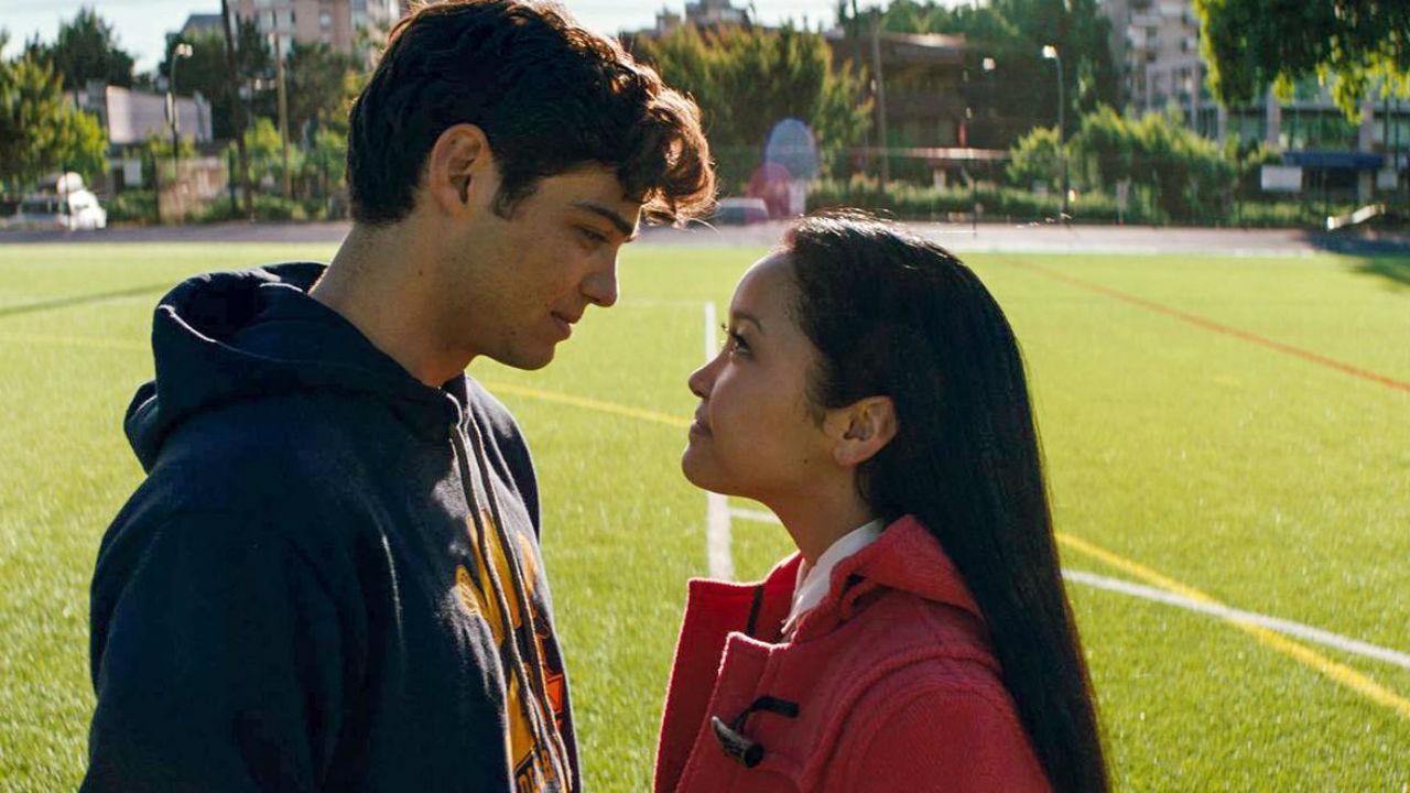 Lara e Peter no campo de futebol sorrindo um para o outro no filme da Netflix.